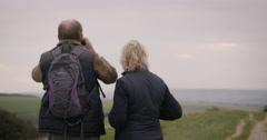 Couple looking through binoculars - stock footage