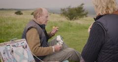 Elderly couple relaxing and having breakfast in field - stock footage