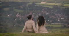 Young couple sitting on hilltop and looking at view Stock Footage