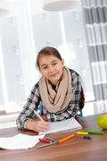 Stock Photo of Little girl working on her school project at home.