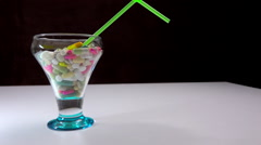 Cocktail glass and straw, cup full of medicine - zoom in, transition Stock Footage
