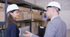 4K Business man & woman in discussion as they walk through industrial warehouse. - stock footage