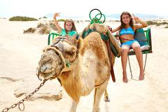 Girls riding Camel in Canary Islands - stock photo