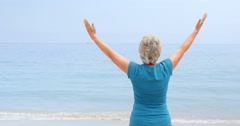 Woman facing the sun with open arms Stock Footage