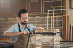Carpenter making a display case with skill and care - stock photo