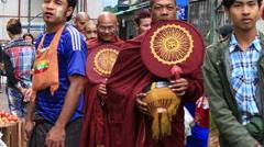 Burmese monks collect alms in the street food market . Yangon, Myanmar, Burma Stock Footage