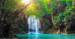 Sunshine and beautiful waterfall flows to wild pond in rain forest of Thailand - stock footage