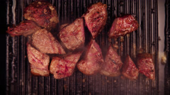 Chunks of steak frying on grill with succulent juices seeping from meat - stock footage