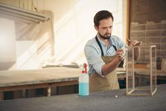 Designer finishing his woodwork project with concentration - stock photo