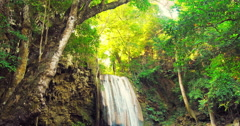 Deep jungle rain forest tropical waterfall and sunlight shines through leaves  - stock footage
