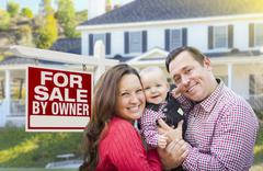Happy Young Family In Front of For Sale By Owner Real Estate Sign and House. Stock Photos