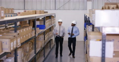 4K 2 Businessmen in discussion as they walk through industrial warehouse. Stock Footage
