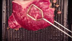 Juicy red steak being flipped on a cast iron grill - stock footage