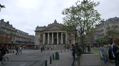 People walking and riding bikes in front of Brussels Stock Exchange building Stock Footage