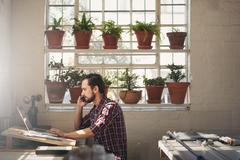 Designer entrepreneur using his phone while working on lapto - stock photo