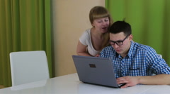 Young man sitting and looking at laptop. He is busy process and pays no Stock Footage