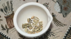 Green cardamom is grinded in a ceramic mortar Stock Footage