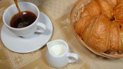 Pouring Coffee into Cup with Croissant - stock footage