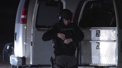 SWAT Tactical Officer Gearing Up at Night Stock Footage