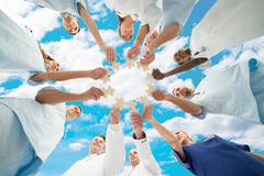 Stock Photo of Directly below shot of medical team joining jigsaw pieces in huddle against s
