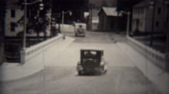 1939: Ford model T car driving across new bridge in small town. Stock Footage