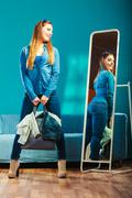 Fashion woman wearing blue denim in front of mirror Stock Photos