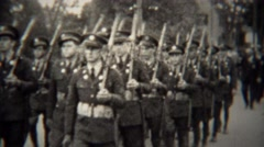 1939: Military soldiers marching with rifles in small town parade. - stock footage