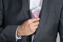 Midsection of businessman putting bribe in suit pocket at office - stock photo