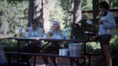 1967: Family cooking breakfast at outdoor camping picnic table. Stock Footage