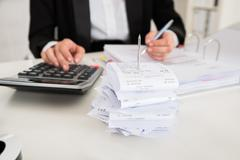 Receipts in paper nail with young businesswoman working at desk Stock Photos