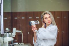 Woman dry hair hairdryer at bathroom. Female with dryer  home Stock Photos