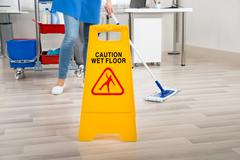 Low section of female janitor mopping floor by yellow wet caution sign in off - stock photo