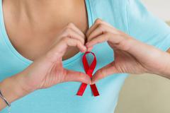 Young woman making heart shape in front of AIDS awareness ribbon at home Stock Photos