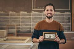 Craftsman entrepreneur proudly displaying a framed bank note - stock photo