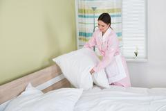 Happy Female Housekeeper Arranging White Pillows On Bed In Room Stock Photos