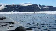 Kayaking towards penguins, fast ice, Antarctica, long Stock Footage