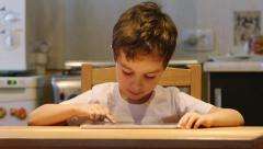 A cute little child uses a tablet PC at a table Stock Footage