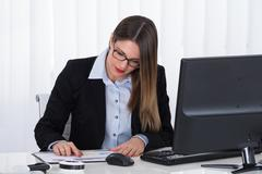 Young Businesswoman Analyzing Financial Report At Office Stock Photos