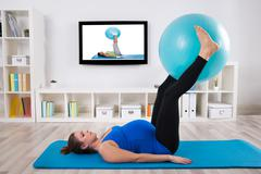 Pregnant Female Exercising With Fitness Ball In Front Of Television - stock photo