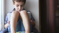 A cute little boy uses a tablet PC on a windowsill - stock footage