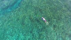 AERIAL tilt down towards surfer paddling towards shipwreck surf break in BALI Stock Footage