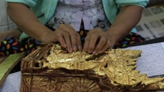 Stock Video Footage of Women coated with gold wooden souvenirs in workshop. Mandalay, Myanmar, Burma