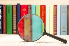 Composition with hardback book and magnifying glass on the table. Back to school Stock Photos
