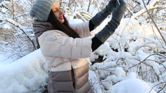 Beautiful happy woman doing self smartphone. Snow covered trees in winter park Stock Footage