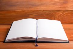 Open book with blank pages on textured wood background. Copy space - stock photo