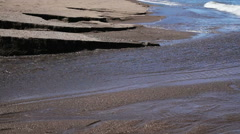 Black sand volcanic beach with creek Stock Footage