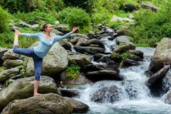 Woman doing yoga asana outdoors at waterfall Stock Photos