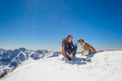 Girl ski touring with his dog at the top of the mountain Stock Photos