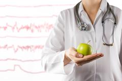 Healthcare and medicine concept - Female doctor's hand holding green apple - stock photo