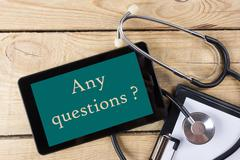 Any questions  - Workplace of a doctor. Tablet, stethoscope, clipboard on wooden Stock Photos